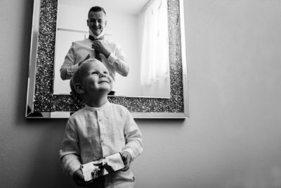 Vőlegény készülődik gyerek segít a nyakkendőkötésben telefonról megy a kisegítő videó