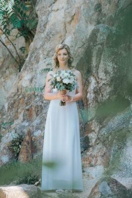 Menyasszony csokorral a kezében a sziklafal előtt