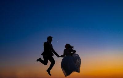Menyassozny és vőlegény boldogan ugrálnak naplementében csodás sziluett