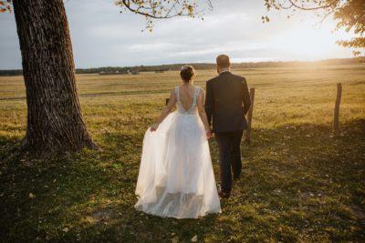 A menyasszony és a vőlegény a naplementében sétálnak.