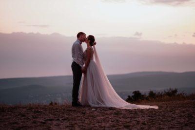 A menyasszony és a vőlegény a naplementében.