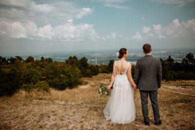 A menyasszony és a vőlegény nézi a várost a Hármashatárhegyről.