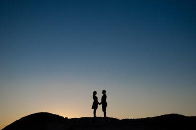 Naplementében egymással szemben áll a pár a domb tetején sziluett