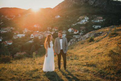 Az ifjú pár a naplementeben gyalogol a hegy tetejénn