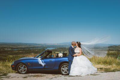 kék cabrio mellett csókolozik az ifjú pár