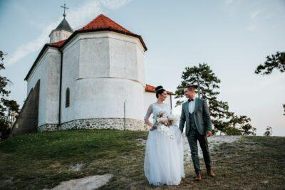 menyasszony és vőlegény az esküvő után gyalogol a templomból