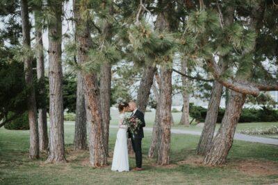menyasszony és vőlegény egymást karolja a fák alatt
