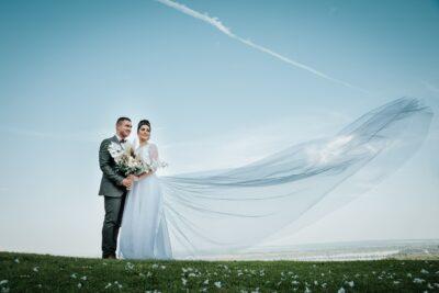 menyasszony fátylát fujja a szél közben a vőlegény ölel